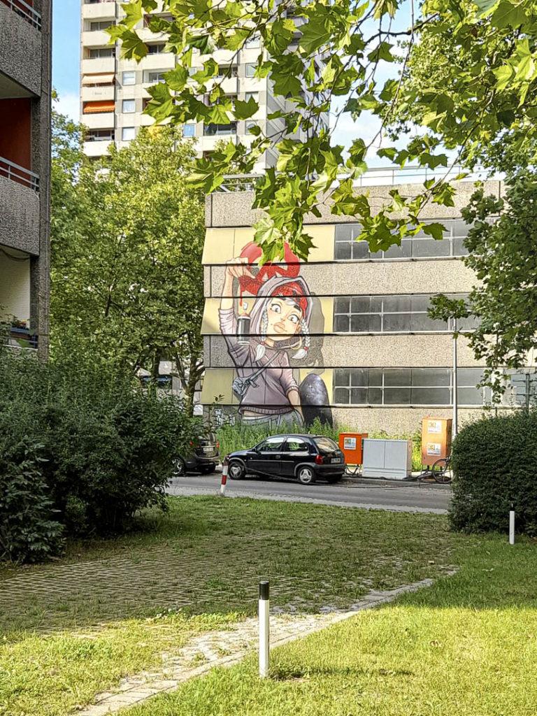 Foto eines Grafitto mit einem coolen Mädchen, das eine Spraydose fallenlässt, in der Gropiusstadt, drumherum grüne Bäume und Hochhäuser